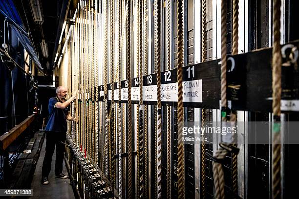 A crew member controls the scenery by pulling on counterweight ropes behind the scenes during a performance of Mother Goose at Hackney Empire on...