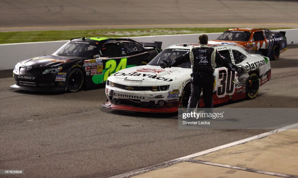 A crew member for Brian Scott (not pictured), driver of the #2 Shore Lodge Chevrolet, confronts <a gi-track='captionPersonalityLinkClicked' href=/galleries/search?phrase=Nelson+Piquet+Jr.+-+Born+1985&family=editorial&specificpeople=235640 ng-click='$event.stopPropagation()'>Nelson Piquet Jr.</a>, driver of the #30 Delavaco Chevrolet, on pit road after the NASCAR Nationwide Series ToyotaCare 250 at Richmond International Raceway on April 26, 2013 in Richmond, Virginia.