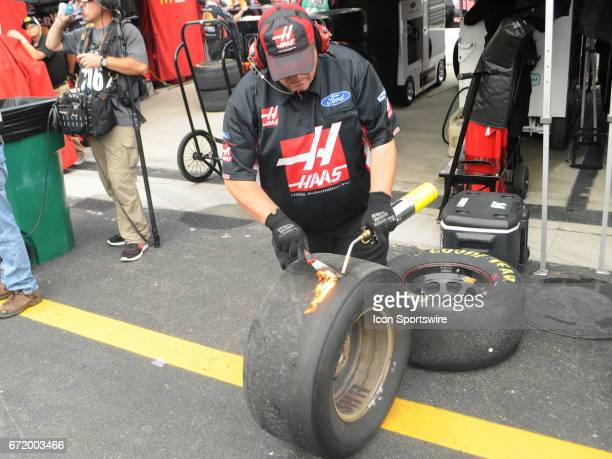 A crew member for Clint Bowyer StewartHass Racing Haas Automation Demo Days Ford Fusion Fusion checks the wear on a tire during practice for the...