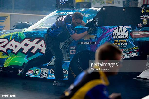 A crew member for driver Courtney Force runs the Funny Car back to the start during day one of the MoPar Mile High Nationals at Bandimere Speedway on...