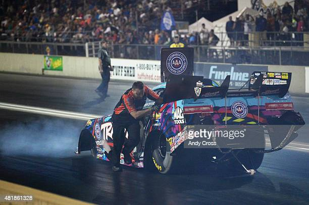 A crew member for NHRA Funny Car driver Courtney Force helps to push her car back to the line for her second qualifying run at the 2015 Mopar Parts...
