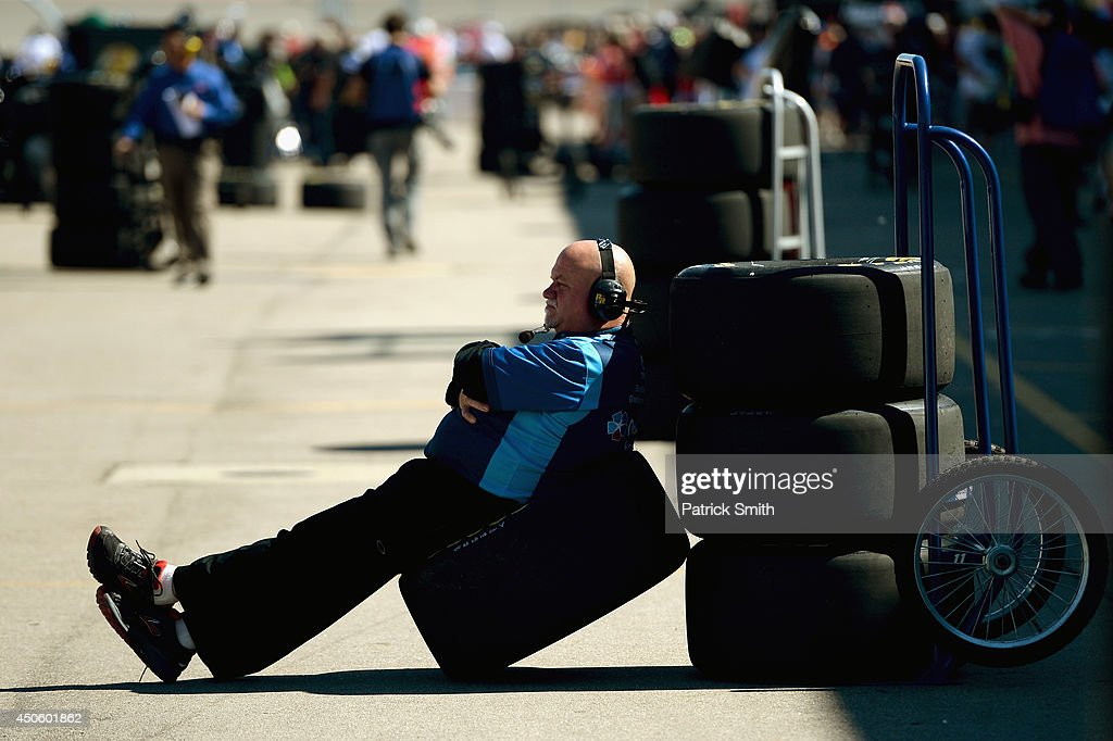 A crew member for the #11 OneMain Financial Toyota, driven by Elliott Sadler, sits on a tire in the pits during qualifying for the NASCAR Nationwide Series Ollie's Bargain Outlet 250 at Michigan International Speedway on June 14, 2014 in Brooklyn, Michigan.