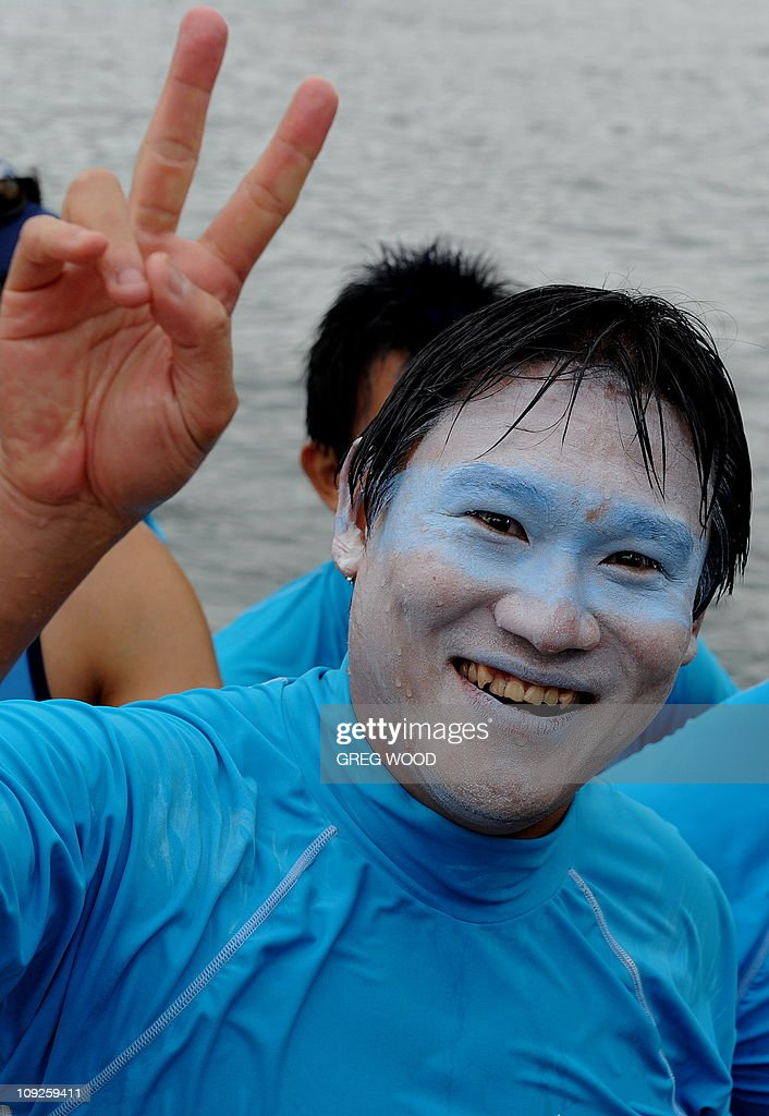 A crew member gestures as he returns to the marina after completing in a Lunar New Year festival dragon boat race on Darling Harbour in Sydney on February 12, 2011. The event, held over two days and billed as the biggest meet in the southern hemisphere, sees more than 3,000 paddlers racing in brilliantly coloured dragon boats. AFP PHOTO / Greg WOOD