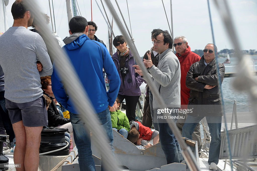 A crew member (3rd R) gives explanations during a public visit on the French Tara Oceans boat on May 18, 2013, in Lorient, western France, on the eve of its departure for a 25.000km tour of the Arctic ocean that will last seven months. French Tara Oceans boat navigates across all the world's major oceans to sample and investigate microorganisms in the largest ecosystem on the planet.