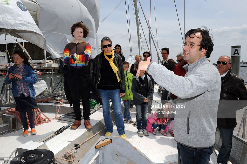 A crew member (2nd L) gives explanations during a public visit on the French Tara Oceans boat on May 18, 2013, in Lorient, western France, on the eve of its departure for a 25.000km tour of the Arctic ocean that will last seven months. French Tara Oceans boat navigates across all the world's major oceans to sample and investigate microorganisms in the largest ecosystem on the planet.