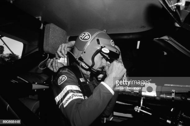 A crew member hooks up radio communications equipment as champion Richard Petty prepares to qualify for the 1980 Daytona 500 stock car race at...