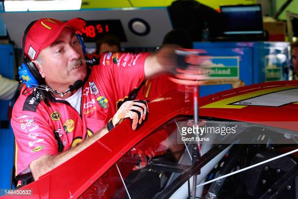 A crew member makes a chassis adjustment to the McDonald's Chevrolet in the garage during practice for the NASCAR Sprint Cup Series Quicken Loans 400...