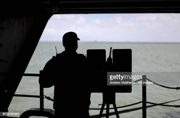 A crew member mans a gun as he keeps look out onboard the US Navy Nimitzclass aircraft carrier USS George HW Bush as it lays at anchor off the coast...