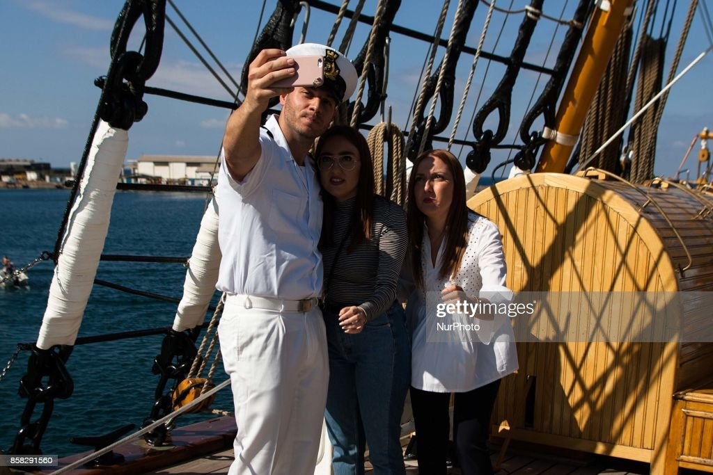 Crew member of Italian sailing ship Amerigo Vespucci takes a selfie with visitors in Naples, Italy, October on 06, 2017.
