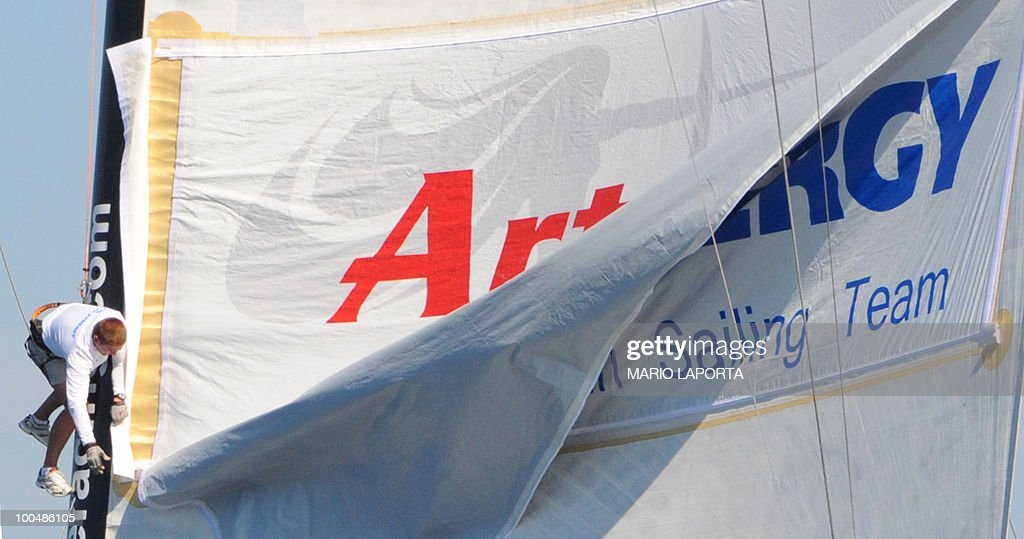 A crew member of Russian team Synergy sailing team changes the banner on the sail at the end of a match race regatta of the Louis Vuitton Trophy on May 24, 2010 at La Maddalena island in Sardinia. Ten teams battle it out over a two-week regatta begun on May 22 until June 6, 2010.