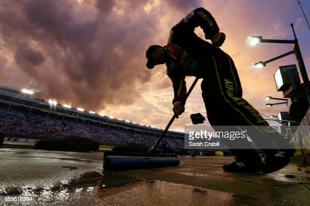 A crew member of the 5Hour ENERGY Extra Strength Toyota dries a pit stall during a rain delay during the Monster Energy NASCAR Cup Series CocaCola...