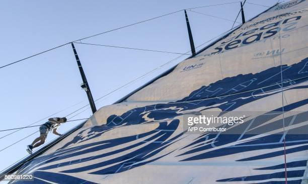 A crew member of the Clean Seas sailboat climbs the mast on October 13 2017 during a training off the coast of Alicante southeastern Spain for the...