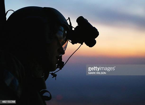 A crew member of the flying support for US Secretary of Defence Chuck Hagel looks out the window of a UH60 Blackhawk helicopter from Bravo Co 2/147th...