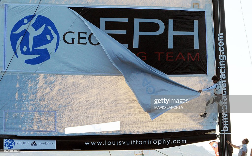 A crew member of the French/German All4One change the banner on the sail at the end of the match race regatta of the Louis Vuitton Trophy on May 24, 2010 at La Maddalena island in Sardinia. Ten teams battle it out over a two-week regatta begun on May 22 until June 6, 2010.