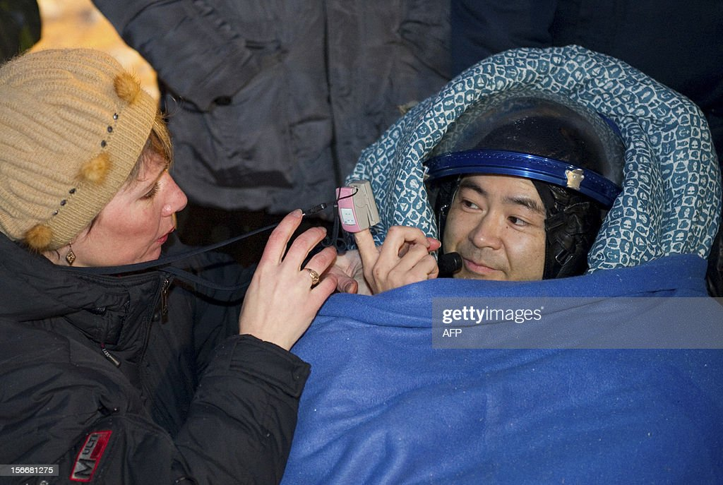 A crew member of the International Space Station (ISS), Akihiko Hoshide of Japan, is assisted shortly after his landing in Soyuz capsule near the town of Arkalyk in northern Kazakhstan, early on November 19, 2012. Russian cosmonaut Yury Malenchenko and two astronauts, Sunita Williams of the US and Akihiko Hoshide of Japan, touched down early today on the steppes of Kazakhstan in a Russian Soyuz capsule after spending over four months aboard the International Space Station (ISS).