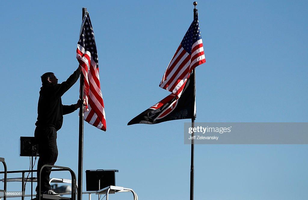 A crew member raises a flag during practice for the NASCAR Camping World Truck Series SFP 250 at Kansas Speedway on April 19, 2013 in Kansas City, Kansas.