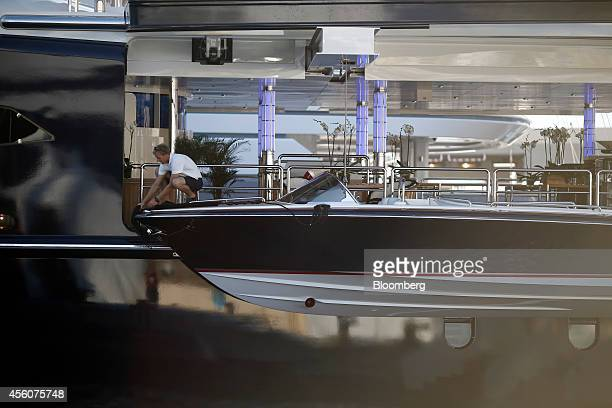 A crew member stands beside a tender boat as it hangs supported by winch from an access door aboard the luxury superyacht Equanimity built by Oceanco...