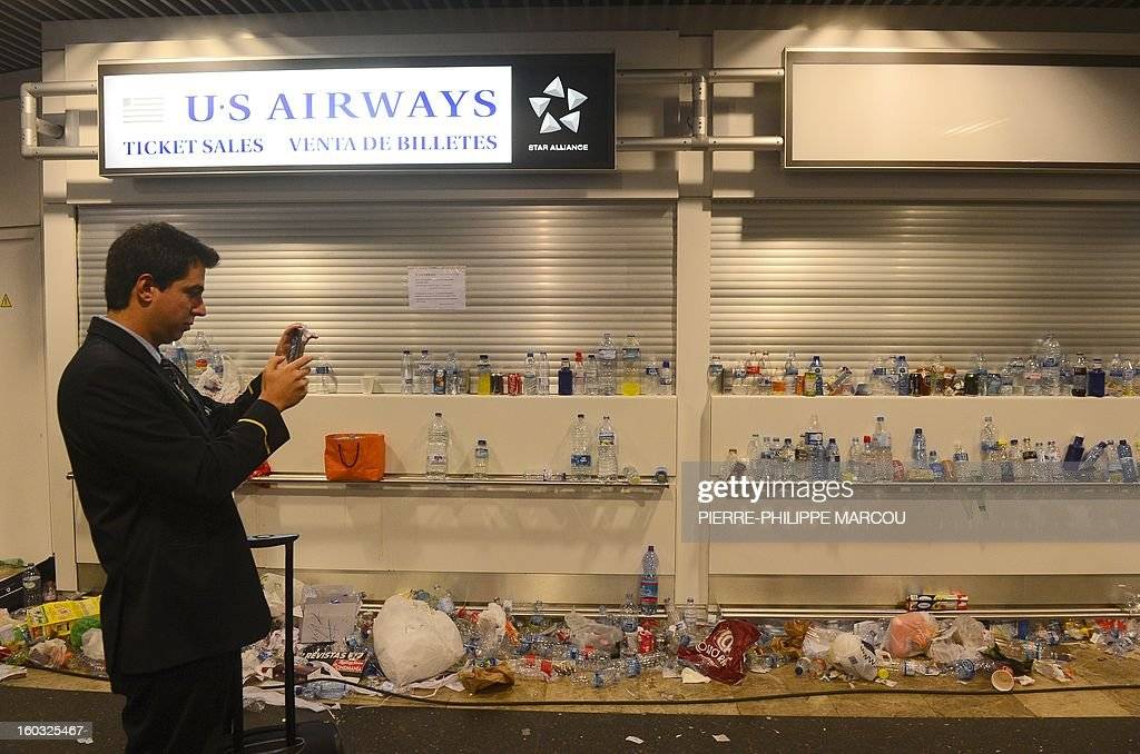 A crew member takes pictures of the rubbish at Barajas airport in Madrid on January 29, 2013. Garbage piled up at Madrid's Barajas airport, one of Europe's busiest, due to a strike by cleaning staff over salary cuts and job losses. MARCOU