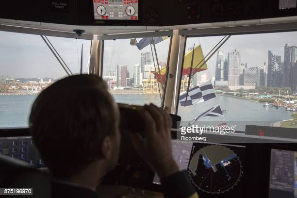 A crew member uses binoculars to look out from the control room aboard the Genting Hong Kong Ltd Genting Dream cruise ship berthed at the Marina Bay...