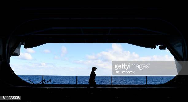 A crew member walks by the open hanger bay on July 14 2017 in Townsville Australia USS Ronald Reagan is a 1092 foot aircraft carrier which carries a...