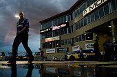 A crew member walks through the staging area with a rainbow overlooking the track during a rain delay at day one of the MoPar Mile High Nationals at...