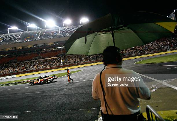 A crew member walks to Mike Bliss driver of the Miccosukee Indian Gaming Resort Chevrolet in his car on pit road in a rain delay during the NASCAR...