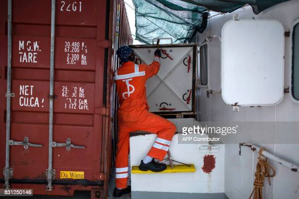 A crew member works on the deck aboard the Aquarius rescue ship on August 14 2017 in the Mediterranean Sea some 20 nautical miles from the Libyan...