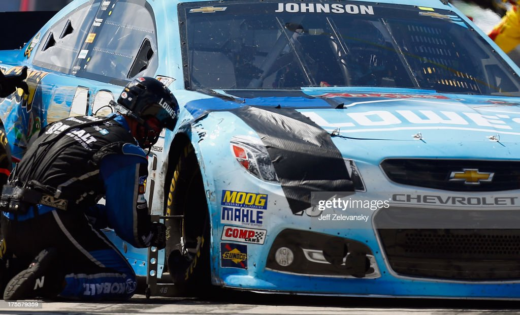 A crew member works on the #48 Lowe's Planes Chevrolet, driven by <a gi-track='captionPersonalityLinkClicked' href=/galleries/search?phrase=Jimmie+Johnson+-+Piloto+da+Nascar&family=editorial&specificpeople=171519 ng-click='$event.stopPropagation()'>Jimmie Johnson</a>, following an incident during the NASCAR Sprint Cup Series GoBowling.com 400 at Pocono Raceway on August 4, 2013 in Long Pond, Pennsylvania.
