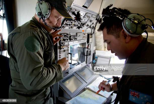 Crew members aboard a Royal Australian Air Force AP3C Orion aircraft observe navigation maps as they search for missing Malaysian Airlines flight...