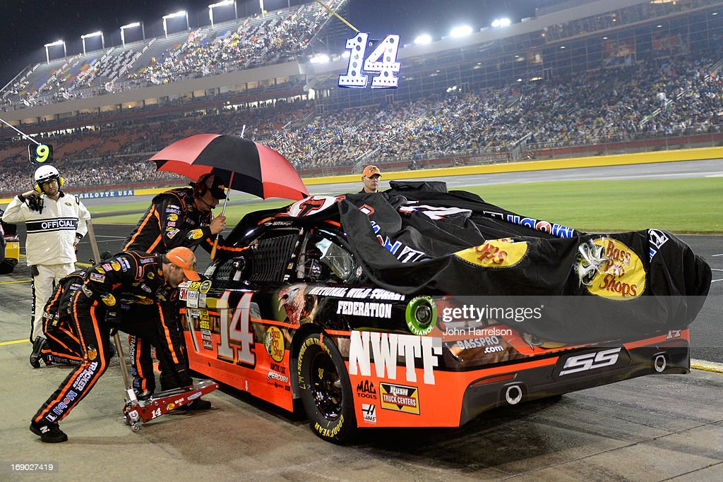 Crew members cover the #14 Bass Pro Shops/NWTF Chevrolet of Tony Stewart during a rain delay in the NASCAR Sprint Cup Series All-Star race at Charlotte Motor Speedway on May 18, 2013 in Concord, North Carolina.