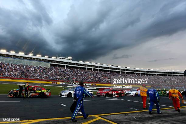Crew members cover the cars during a weather delay during the Monster Energy NASCAR Cup Series CocaCola 600 at Charlotte Motor Speedway on May 28...