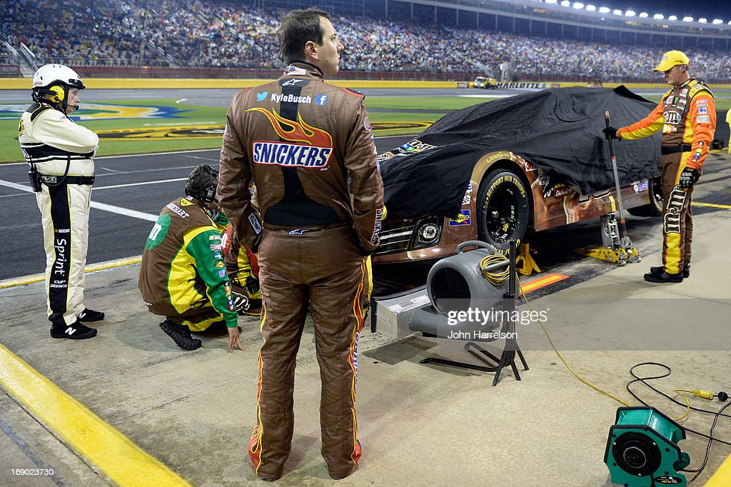 Crew members cover the #18 Snickers Bites Toyota of Kyle Busch as he looks on during a rain delay in the NASCAR Sprint Cup Series All-Star race at Charlotte Motor Speedway on May 18, 2013 in Concord, North Carolina.