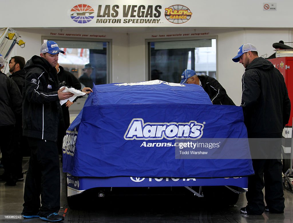 Crew members dry the #55 Aaron's Dream Machine Toyota, driven by Mark Martin, in the garage before practice for the NASCAR Sprint Cup Series at Las Vegas Motor Speedway on March 8, 2013 in Las Vegas, Nevada.
