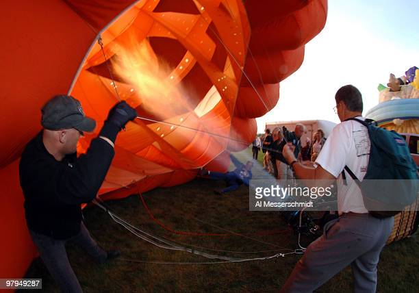 Crew members fire up a pumpkin balloon for an evening glowdoe event at the Albuquerque International Balloon Fiesta October 6 1005