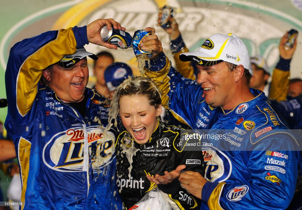 Crew members for Brad Keselowski, driver of the #2 Miller Lite Dodge, celebrate with Miss Sprint Kim Coon in Victory Lane after Keselowski won the NASCAR Sprint Cup Series Quaker State 400 at Kentucky Speedway on June 30, 2012 in Sparta, Kentucky.