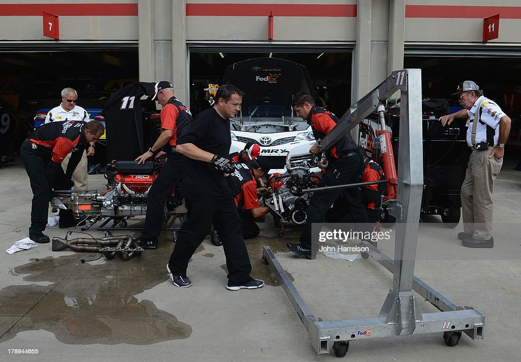 Crew members for Denny Hamlin, driver of the #11 SportClips Toyota, make a motor change during practice for the NASCAR Sprint Cup Series AdvoCare 500 at Atlanta Motor Speedway on August 31, 2013 in Hampton, Georgia.