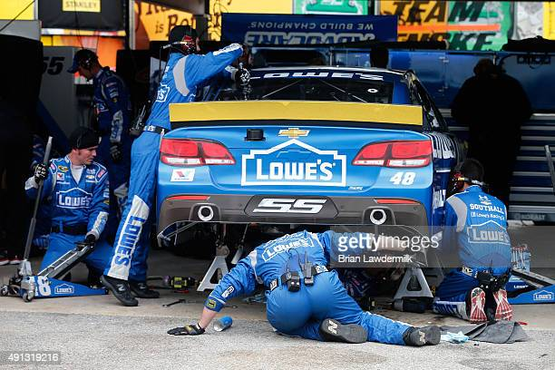 Crew members for Jimmie Johnson driver of the Lowe's Chevrolet work to repair his car in the garagea during the NASCAR Sprint Cup Series AAA 400 at...