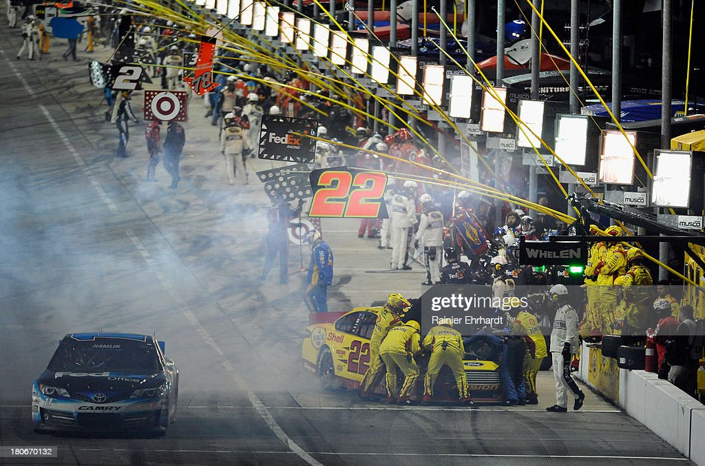 Crew members for Joey Logano, driver of the #22 Shell-Pennzoil Ford, work on his car as Denny Hamlin, driver of the #11 FedEx Office Toyota, leaves pit lane during the NASCAR Sprint Cup Series Geico 400 at Chicagoland Speedway on September 15, 2013 in Joliet, Illinois.