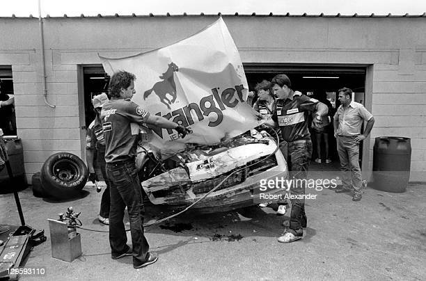 Crew members for NASCAR driver Dale Earnhardt Sr work on the driver's damaged car after an accident during the 1986 Daytona 500 on February 16 1986...