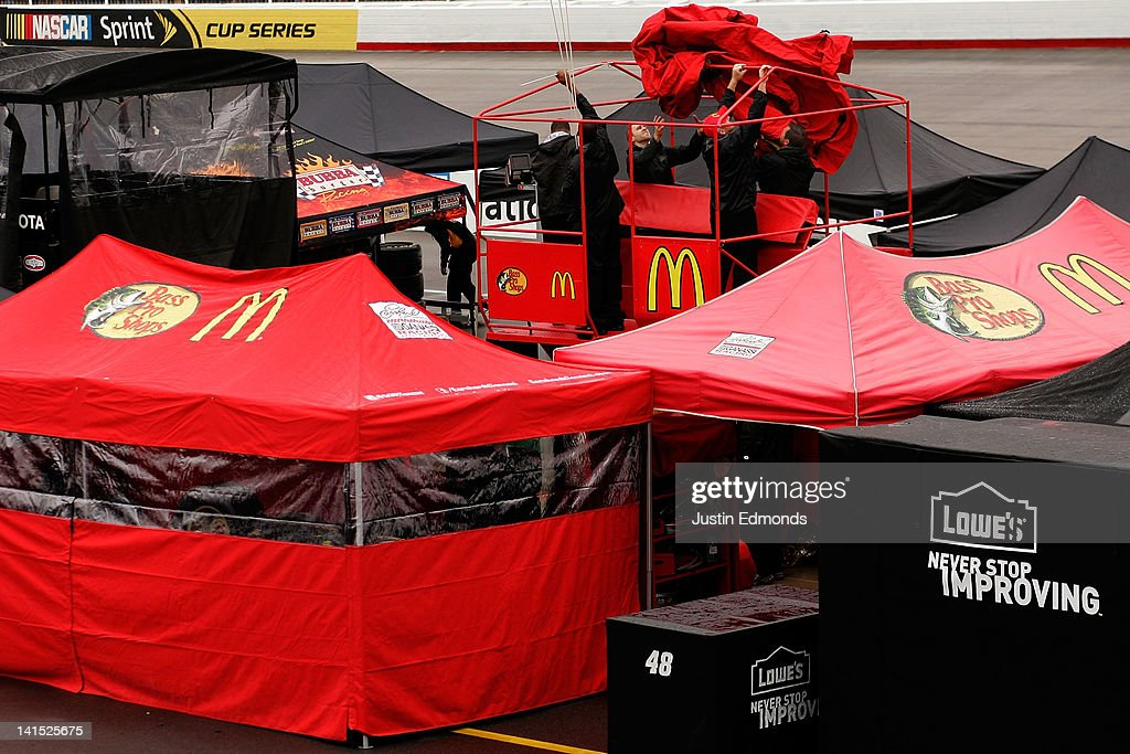 Crew members for the #1 McDonald's Chevrolet driven by Jamie McMurray install a cover on their pit box to protect it from the rain prior to the NASCAR Sprint Cup Series Food City 500 at Bristol Motor Speedway on March 18, 2012 in Bristol, Tennessee.