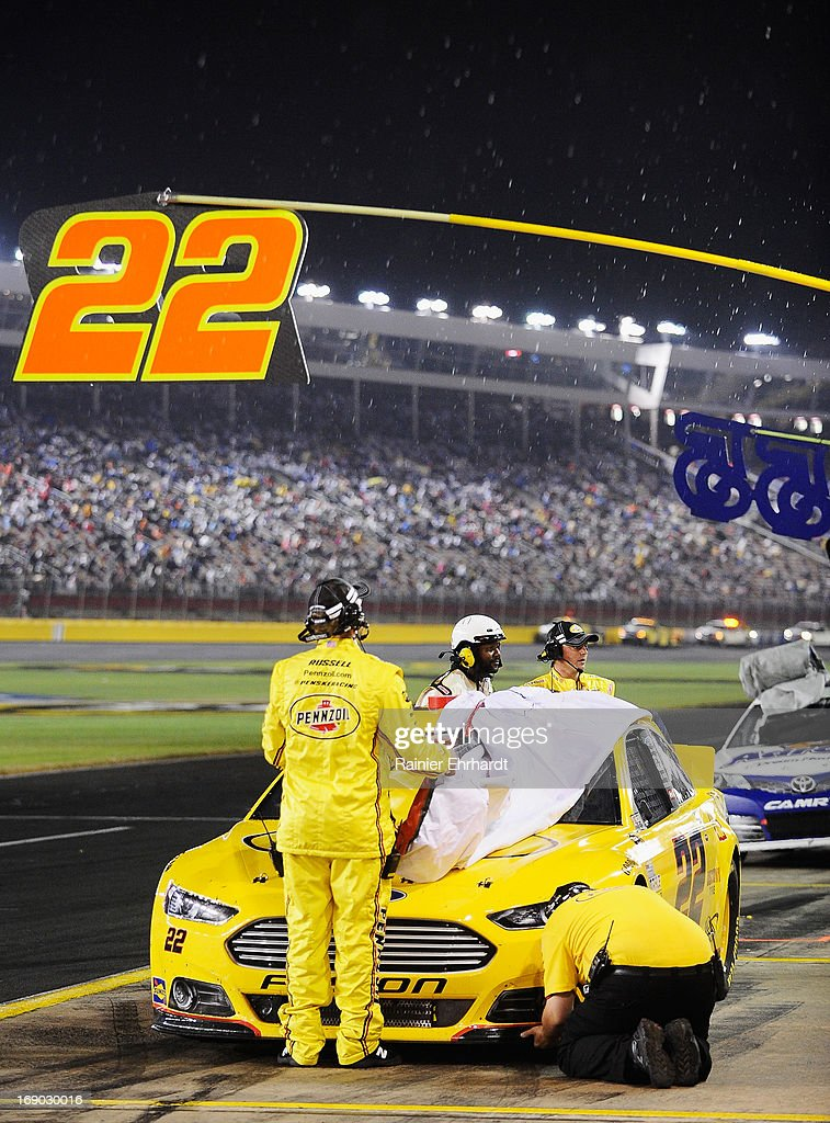 Crew members for the #22 Pennzoil Ford, cover the car as rain falls during the NASCAR Sprint Cup Series All-Star race at Charlotte Motor Speedway on May 18, 2013 in Concord, North Carolina.
