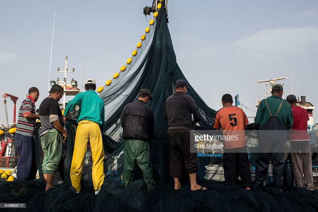 Crew members from the fishing vessel Haddaf II, which rescued more than 40 migrants in 2015 clean the boast nets after arriving in port on June 30, 2016 in Zarzis, Tunisia. Since 2012, the Tunisian border town of Zarzis has dealt with the overflow of migrants from Libya. In 2015 with pressure from EU nations, Tunisia tightened its border security with Libya, cutting the number of migrants arriving in Tunisian border towns. Local fishermen from the Zarzis port who were trained in rescue techniques by MSF in 2015 after being involved in weekly rescues, have seen no rescues so far in 2016, primarily due to an increase in rescue boats from international NGOÕs, coastguards and military vessels patrolling the waters off the Libyan coast. However with an estimated 800,000 migrants waiting in Libya to attempt the dangerous crossing to Europe, preparations were made for an expected increase in rescues and arrivals to Tunisia ahead of the 2016 peak season