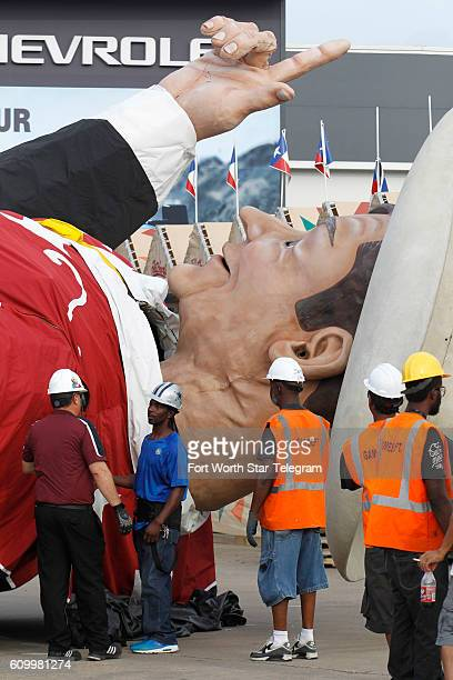Crew members gather near Big Tex's head to secure lifting cables before a crane hoists him into place with the State Fair of Texas one week away from...