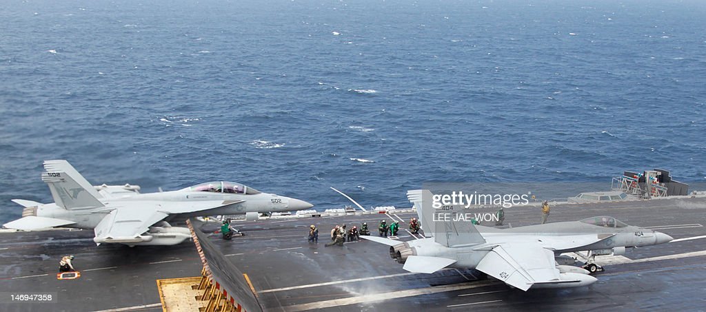Crew members guide US Navy F/A-18 Super Hornet fighters taking off from the deck of the US aircraft carrier USS George Washington during joint military drills between the US and South Korea in the Yellow Sea, southwest of Seoul on June 24, 2012. The three-day drill, which started on June 23, involves 10 South Korean warships plus the USS George Washington aircraft carrier, 8,000 personnel and hundreds of combat aircraft, South Korea's defence ministry said. AFP PHOTO / POOL / Lee Jae-Won