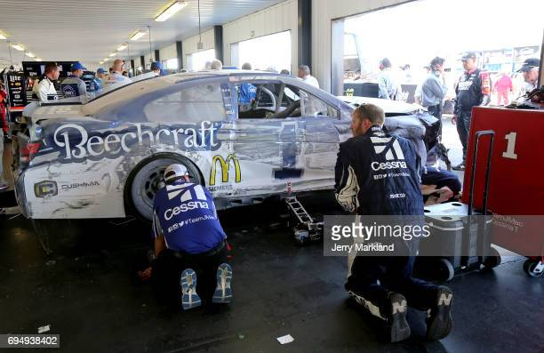 Crew members look over the Cessna Chevrolet driven by Jamie McMurray after it was involved in an ontrack incident during the Monster Energy NASCAR...