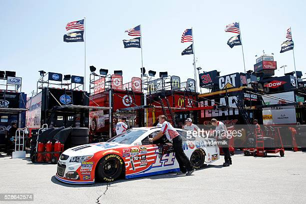 Crew members move the car of Tony Stewart driver of the Mobil 1 Chevrolet during practice for the NASCAR Sprint Cup Series Go Bowling 400 at Kansas...