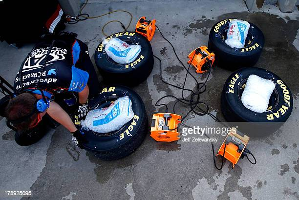 Crew members of Austin Dillon's AdvoCare Spark Chevrolet use ice to cool tires heated up during practice for the NASCAR Nationwide Series Great...