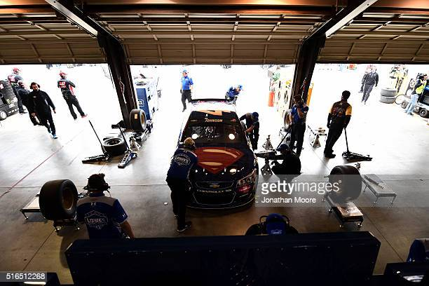 Crew members of Jimmie Johnson driver of the Lowe's / Superman Chevrolet work on the car in the garage area during practice for the NASCAR Sprint Cup...