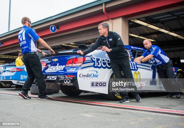 Crew members of Monster Energy NASCAR Cup Series driver Jamie McMurray push out his car from the garage to the track at the NASCAR Monster Energy Cup...