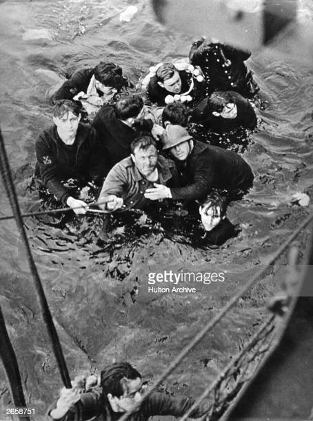 Crew members of the French destroyer Bourrasque sunk by mine at Dunkirk are hauled aboard a British vessel from their sinking liferaft